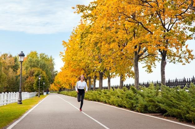 Vrouw die in de herfstbos loopt. jong volwassen meisje joggen in herfstkleuren, camera kijken en brede glimlach.