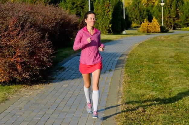 Vrouw die in de herfstpark loopt, mooie meisjesagent die in openlucht aanstoot. uitoefening en fitness concept