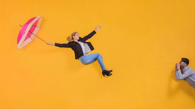 Vrouw die in de lucht met een paraplu drijft