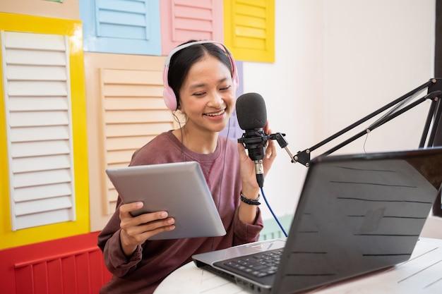 Vrouw die in de microfoon spreekt tijdens het opnemen van een videoblog voor haar abonnees