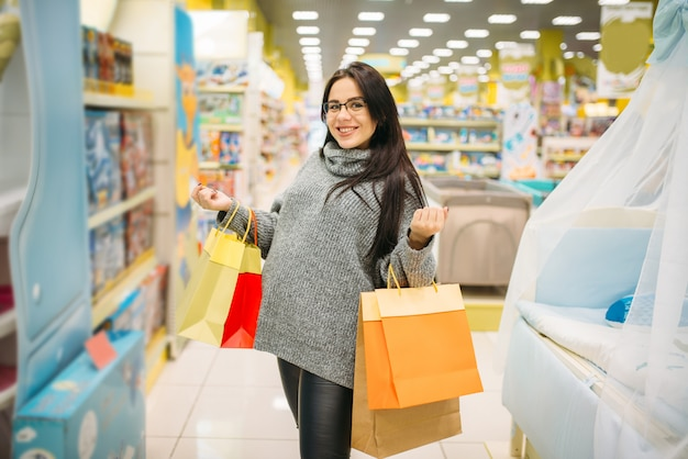 Vrouw die in de opslag voor zwangere vrouwen winkelt. toekomstige moeder in winkel met goederen voor nieuwe brandwonden