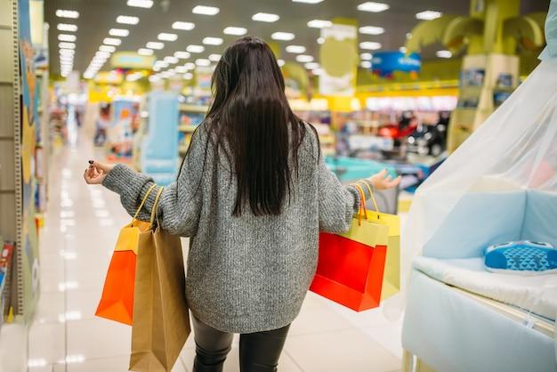 Vrouw die in de opslag voor zwangere vrouwen winkelt