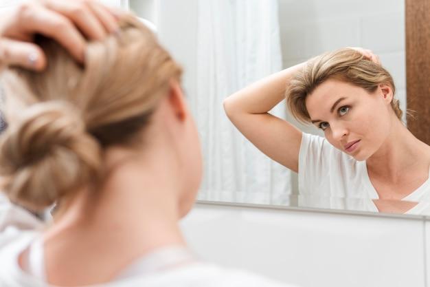 Vrouw die in de spiegel en het uitrekken kijkt