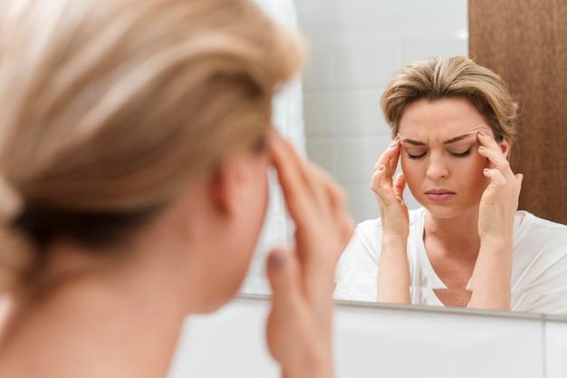 Vrouw die in de spiegel kijkt en een hoofdpijn heeft