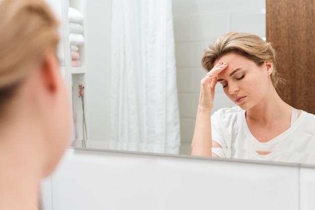 Vrouw die in de spiegel kijkt en een migraine heeft