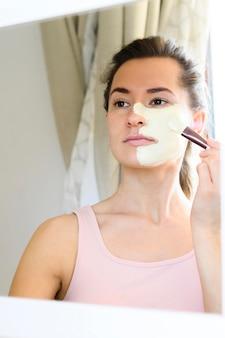 Vrouw die in de spiegel kijkt en gezichtsmasker toepast