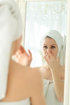 Vrouw die in de spiegel met handdoek op haar hoofd na douche kijkt