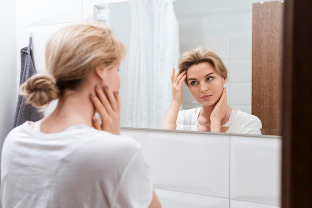 Vrouw die in de spiegel van achter mening kijkt