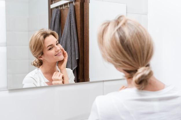 Vrouw die in de spiegel van het achter schot kijkt
