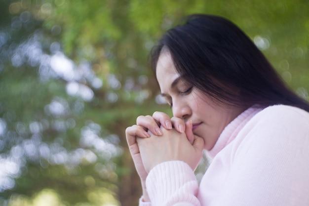 Vrouw die in de tuin, aziatische vrouw met witte kleding bidden