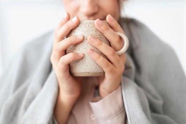 Vrouw die in de winter een slokje thee uit de mok neemt