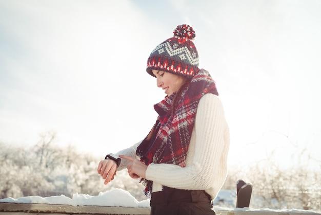 Vrouw die in de winterslijtage haar smartwatch controleert