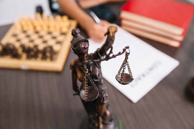 Vrouw die in document bij lijst met standbeeld, boeken en schaak schrijft