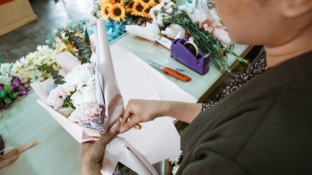 Vrouw die in een bloemenwinkel werkt en een flanelbloem voor een bestelling klaarmaakt in een tafelwerkruimte