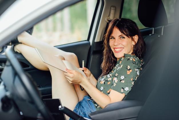 Vrouw die in een notitieboekje met een pen in een witte auto schrijft