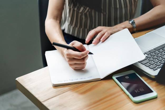 Vrouw die in een notitieboekje schrijft