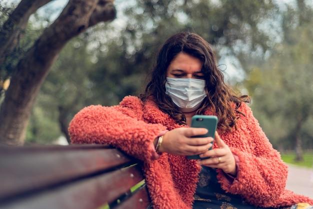 Vrouw die in een park zit, beschermt zichzelf met een medisch masker tijdens het typen op haar smartphone.