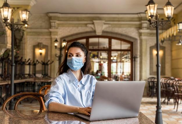 Vrouw die in een restaurant werkt terwijl ze een gezichtsmasker draagt