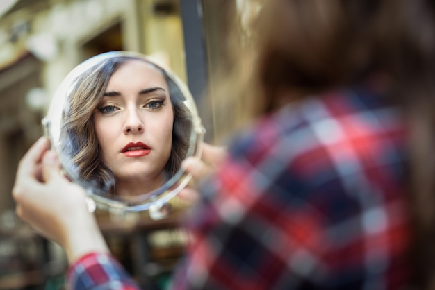 Vrouw die in een spiegel