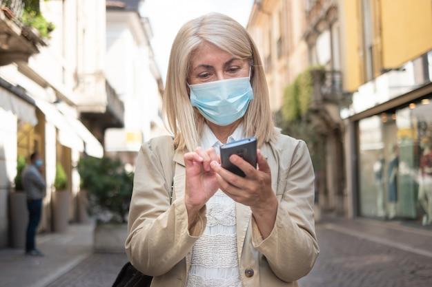Vrouw die in een stadsstraat lopen terwijl het gebruiken van haar smartphone tijdens pandemie van het coronavirus