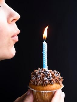 Vrouw die in een verjaardagskaars blaast