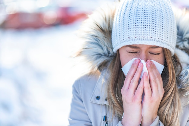 Vrouw die in een weefsel in de koude winter met een sneeuwberg op de achtergrond blaast