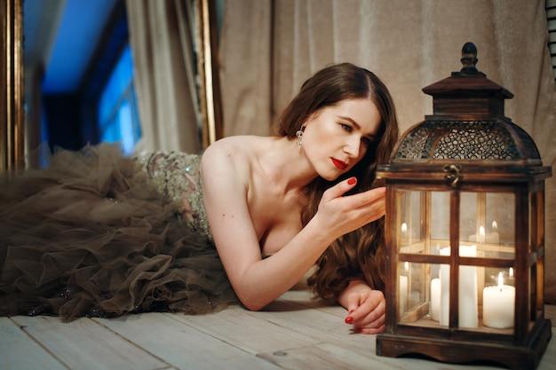 Vrouw die in elegante kleding in lantaarn kijkt