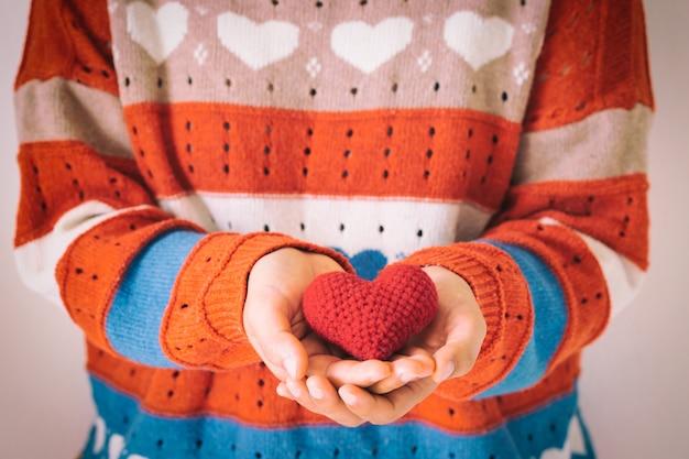 Vrouw die in gebreid overhemd rood hart houdt. concept van liefde en zorg