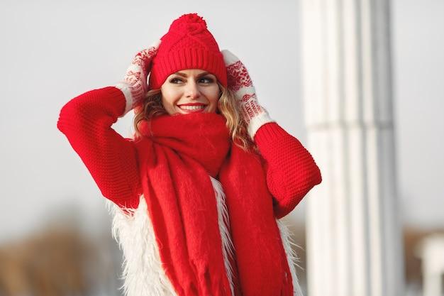 Vrouw die in gebreide de wintermuts en sjaal camera met glimlach bekijkt