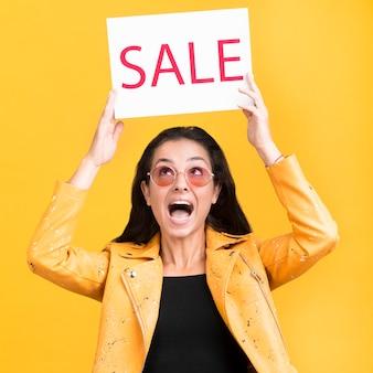 Vrouw die in geel jasje een middelgroot schot van de verkoopbanner houdt