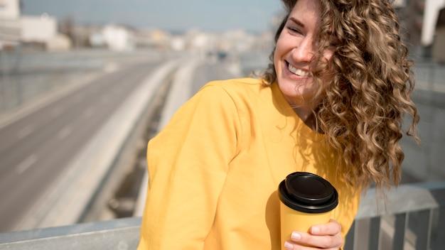 Vrouw die in geel overhemd een kop van koffie houdt
