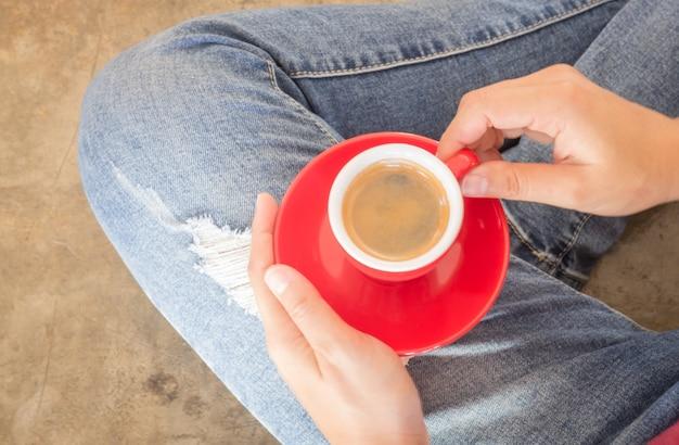 Vrouw die in gescheurde jeans bij koffiewinkel zitten