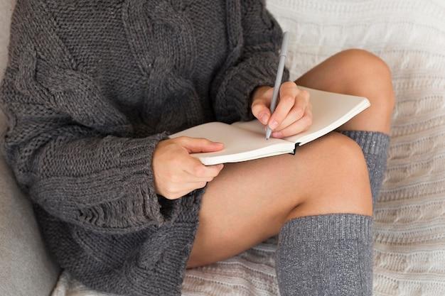 Vrouw die in gezellige kleren in agenda schrijft