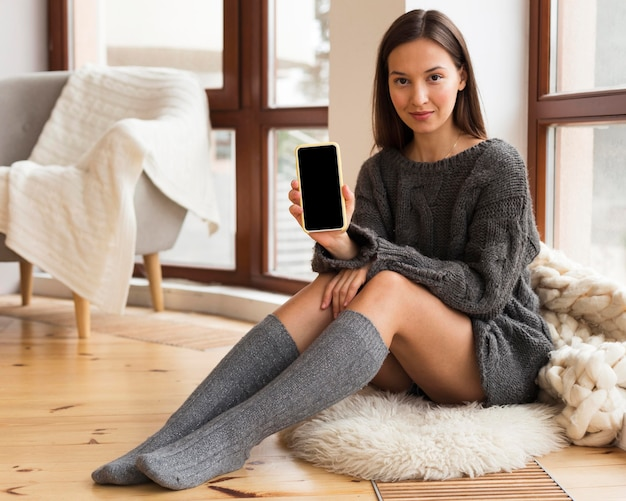 Vrouw die in gezellige kleren op tapijt met lege telefoon zit
