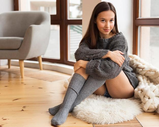 Vrouw die in gezellige kleren op tapijt zit