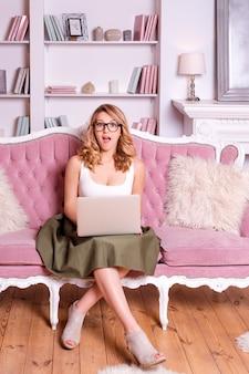 Vrouw die in glazen aan computer werkt die verrast kijkt. casual blogger vrouw met laptop, thuis werken, vrouwelijke business.