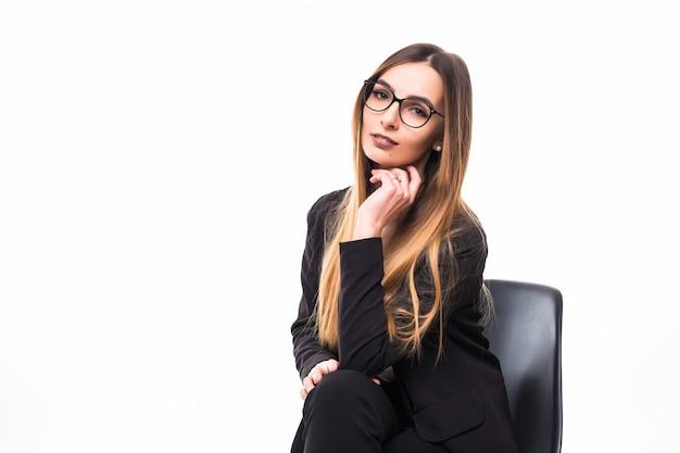 Vrouw die in glazen op een zwarte stoel op wit zit