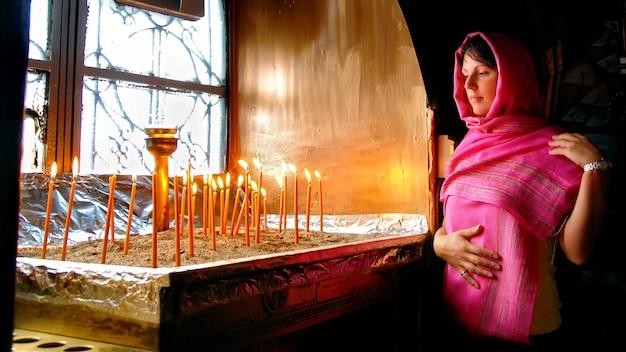 Vrouw die in griekse kerk brandende kaarsen bekijkt