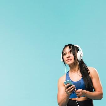 Vrouw die in gymnastiekuitrusting aan muziek in hoofdtelefoons luistert