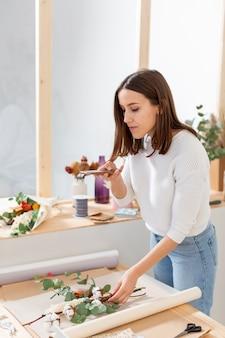 Vrouw die in haar bloemenwinkel een boeket maakt