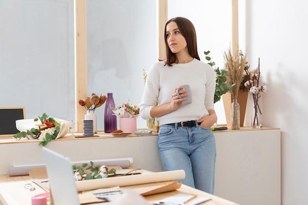 Vrouw die in haar bloemenwinkel weg kijkt