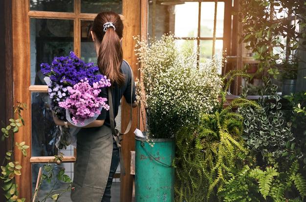 Vrouw die in haar bloemwinkel werkt