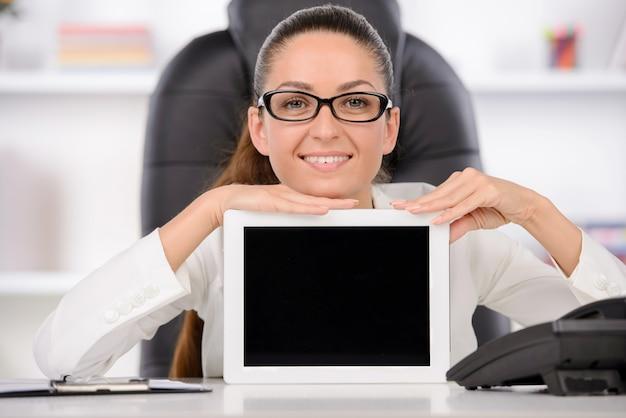 Vrouw die in haar bureau een tabletcomputer voorstelt.