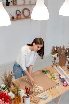 Vrouw die in haar eigen bloemenwinkel werkt