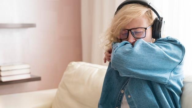 Vrouw die in haar elleboog niest