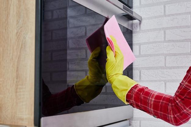 Vrouw die in handschoenen fornuis in de moderne keuken schoonmaken