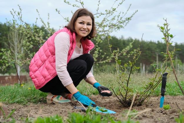 Vrouw die in handschoenen met tuingereedschap werkt, bemest de grond
