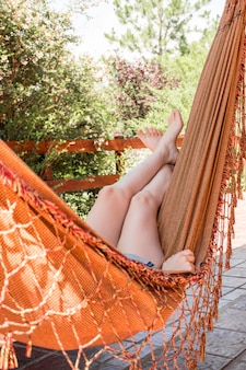 Vrouw die in hangmat op terras ligt