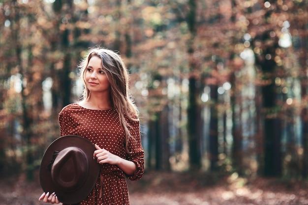 Vrouw die in herfstbos loopt