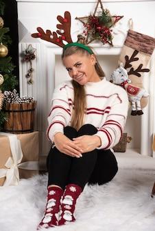 Vrouw die in hertenoren op tapijt dichtbij de kerstboom zit.
